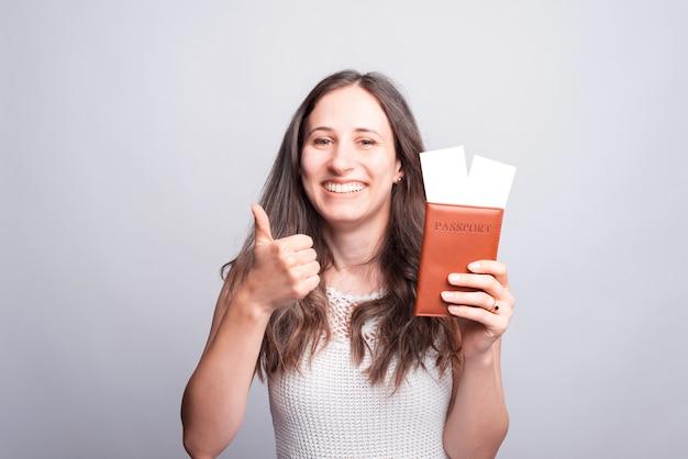 Retrato de mujer feliz mostrando el pulgar hacia arriba y el pasaporte con billetes de avión