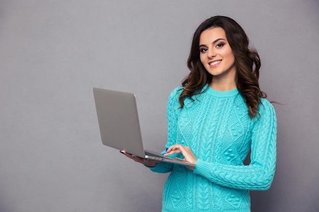 Retrato de una mujer feliz con ordenador portátil sobre pared gris