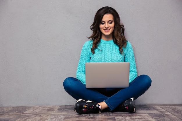 Retrato de una mujer feliz con ordenador portátil en el suelo