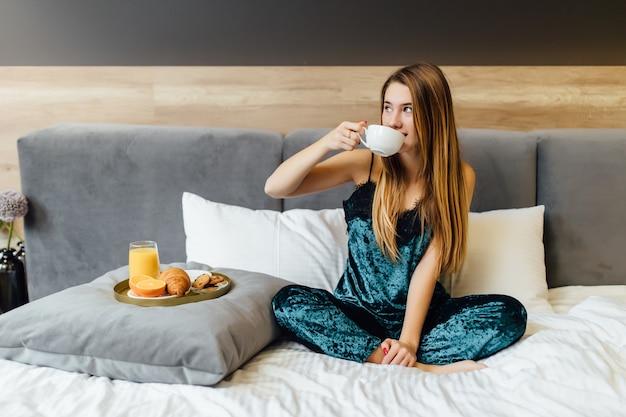Retrato de una mujer feliz pensando y mirando a otro lado en el desayuno de vacaciones en el dormitorio