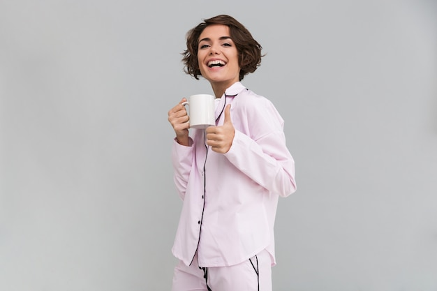 Retrato de una mujer feliz en pijama sosteniendo una taza