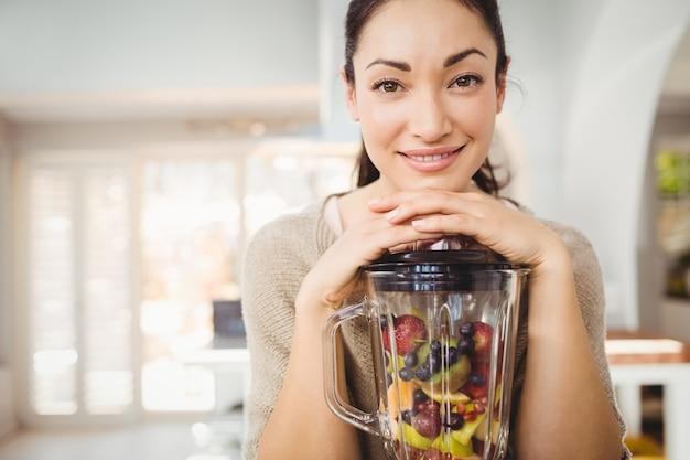 Retrato de mujer feliz preparando zumo de fruta