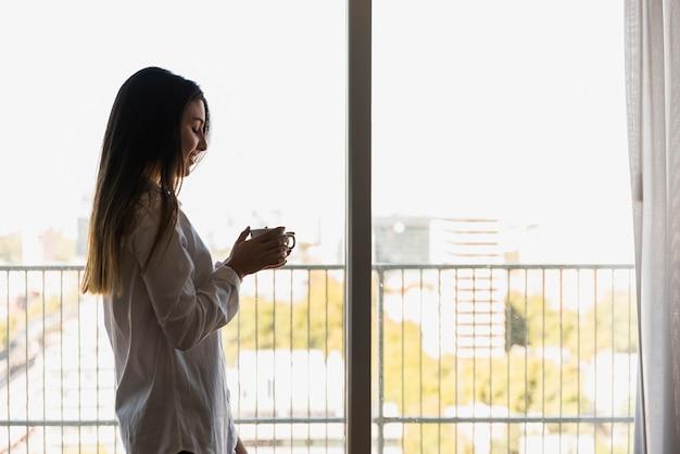 Retrato de una mujer feliz que se coloca en el balcón que sostiene la taza de café disponible