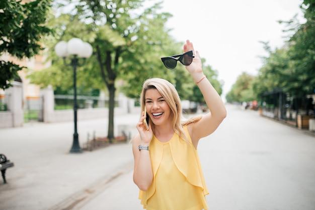 Retrato de una mujer feliz que habla en el teléfono móvil y que agita en la calle de la ciudad.