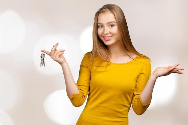 Retrato de la mujer feliz que lleva a cabo llaves