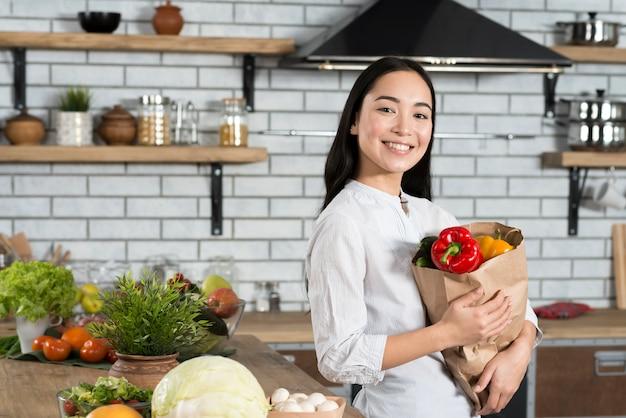 Retrato de la mujer feliz que sostiene el bolso de ultramarinos que se coloca en cocina