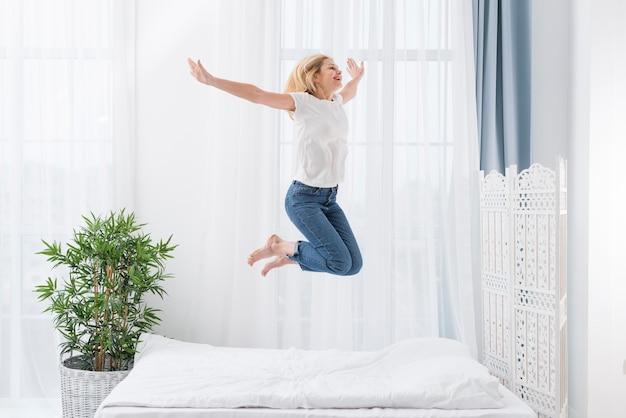 Retrato de mujer feliz saltando en la cama
