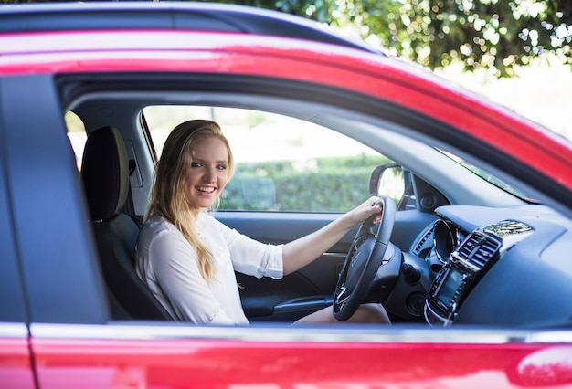 Retrato de una mujer feliz sentada dentro de coche