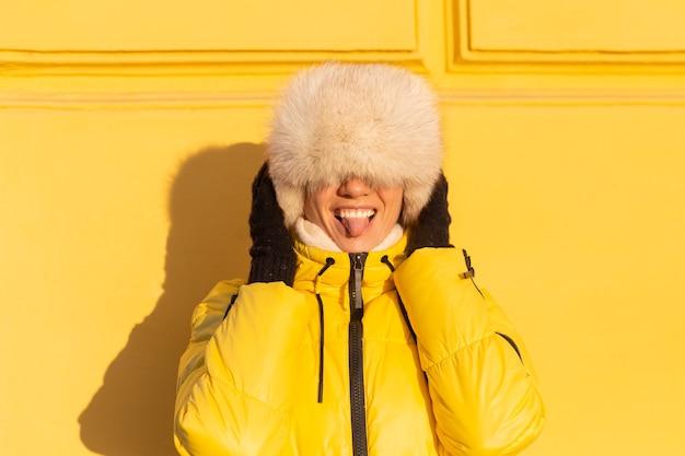 Retrato de una mujer feliz con una sonrisa en zabas blancas como la nieve en invierno contra una pared amarilla en un día soleado en un cálido sombrero siberiano ruso