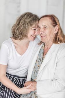 Retrato de mujer feliz sosteniendo la mano de su abuela en casa