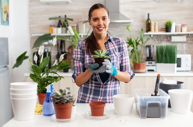 Retrato de mujer feliz sosteniendo plantas suculentas sentado en la mesa en la cocina