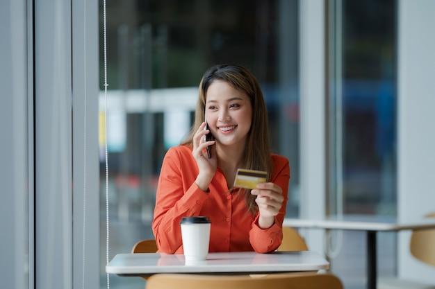 Retrato de mujer feliz sosteniendo teléfono inteligente con tarjeta de crédito y cara sonriente en la oficina creativa o cafetería en el centro comercial