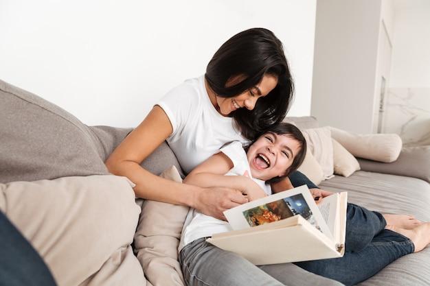 Retrato de mujer feliz con su pequeña hija jugando y divirtiéndose, mientras descansa en casa