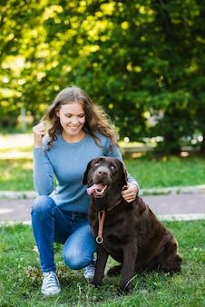 Retrato de una mujer feliz y su perro en el jardín