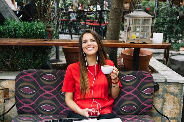 Retrato de una mujer feliz con una taza de café escuchando música en un teléfono inteligente