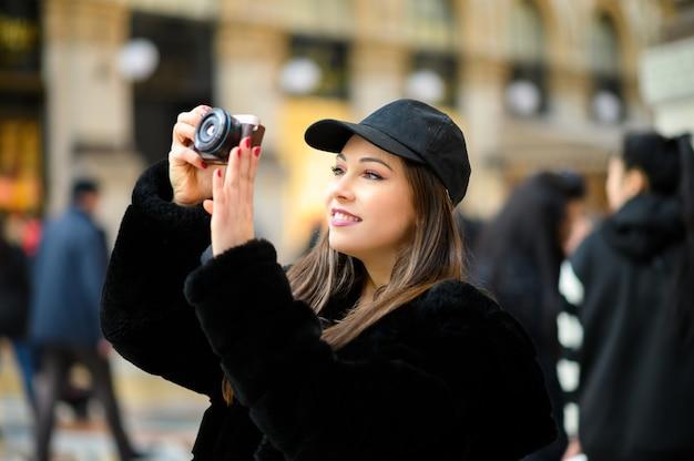 Retrato de mujer feliz tomando fotos con una cámara sin espejo