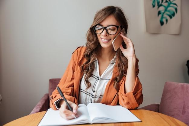 Retrato de una mujer feliz tomando notas