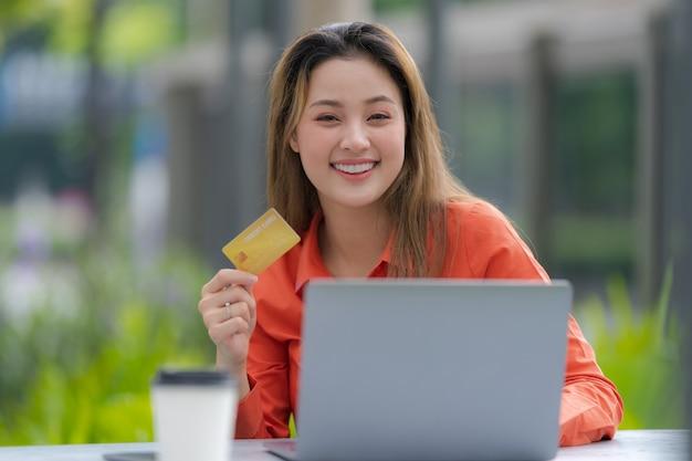 Retrato de mujer feliz usando laptop con tarjeta de crédito y cara sonriente en el parque del centro comercial