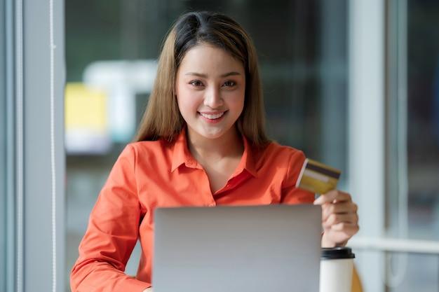 Retrato de mujer feliz usando laptop con tarjeta de crédito y rostro sonriente en oficina creativa o café en el centro comercial