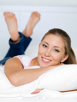 Retrato de mujer feliz yace sobre una almohada en la cama