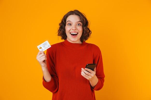 Retrato de mujer femenina con suéter usando teléfono celular y tarjeta de crédito mientras está de pie aislado en amarillo