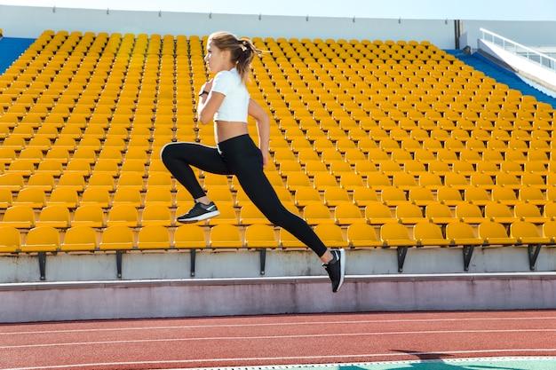 Retrato de una mujer fitness corriendo en el estadio