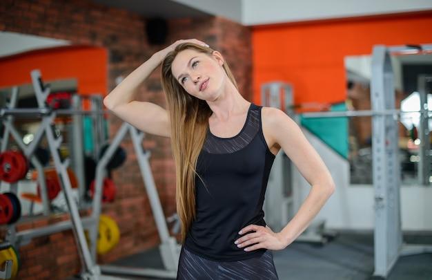 Retrato de mujer fitness estiramientos en el gimnasio antes de entrenar