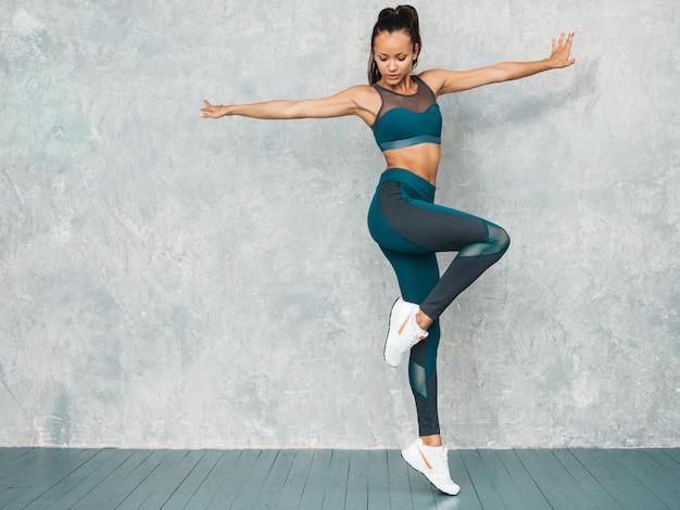 Retrato de mujer fitness en ropa deportiva buscando confianza. joven mujer vistiendo ropa deportiva. hermosa modelo con cuerpo bronceado perfecto. salto femenino en estudio cerca de la pared gris
