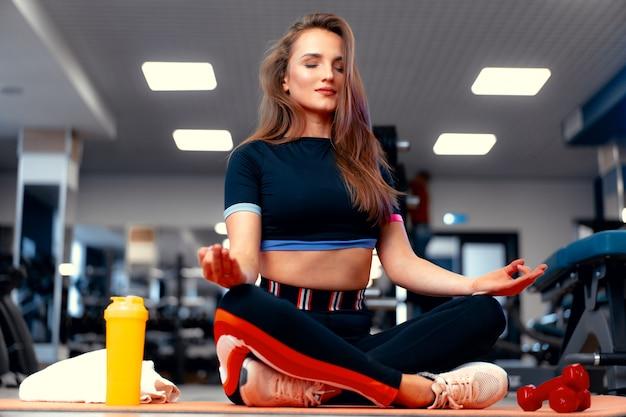 Retrato de mujer fitness trainer sobre un fondo de gimnasio
