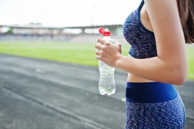 Retrato de una mujer en forma de agua potable después de correr en el estadio.