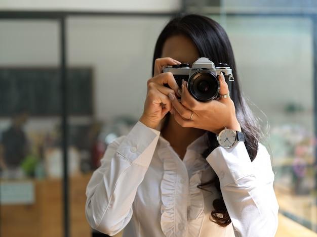 Retrato de mujer fotógrafa tomando fotos con cámara en estudio