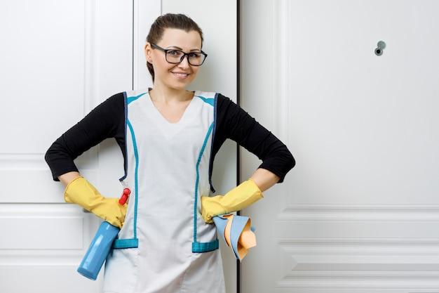 Retrato de mujer con gafas y delantal para limpiar guantes de goma con detergentes