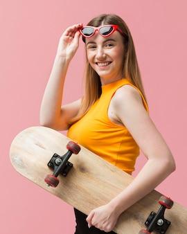 Retrato de mujer con gafas de sol y patineta