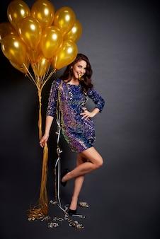 Retrato de mujer glamorosa con globos dorados