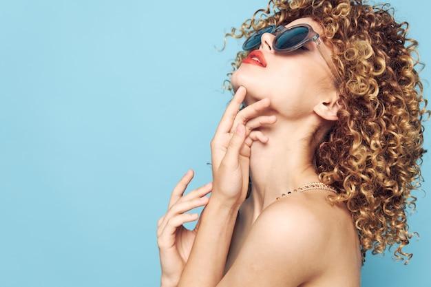 Retrato de una mujer glamour de pelo rizado buscar labios rojos gafas de sol fondo azul aislado