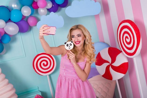 Retrato de mujer golosa increíble en vestido rosa sosteniendo caramelos y posando sobre fondo decorado con helado enorme. panda piruleta