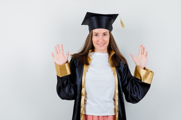 Retrato de mujer graduada mostrando las palmas en gesto de rendición en uniforme, ropa casual y mirando confiada vista frontal