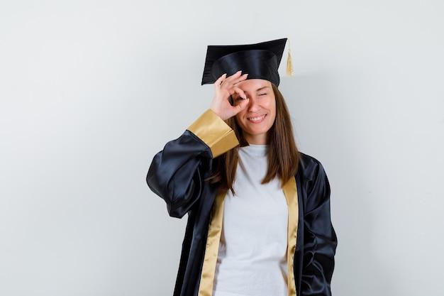 Retrato de mujer graduada mostrando signo de ok en el ojo en bata, ropa casual y mirando confiado vista frontal