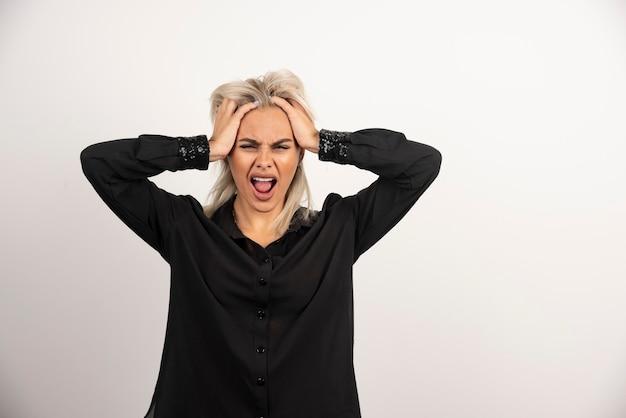 Retrato de mujer gritando en camisa negra posando sobre fondo blanco. foto de alta calidad