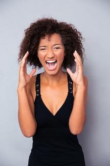 Retrato de mujer gritando sobre pared gris
