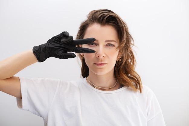 Retrato de una mujer con guantes de goma negros haciendo el signo de la paz sobre su ojo sobre fondo blanco.
