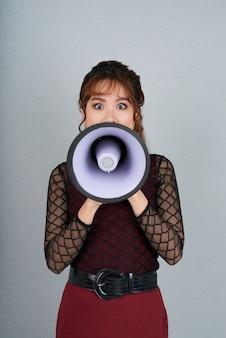 Retrato de mujer haciendo un anuncio a través del altavoz