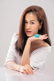 Retrato de mujer hermosa asiática presentando crema para la cara; perfección rejuvenecimiento revitalización hidratante y concepto de cuidado de la piel. modelo que muestra un producto de belleza a mano