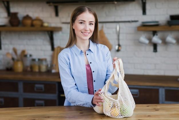 Retrato de mujer hermosa con bolsa reutilizable con frutas