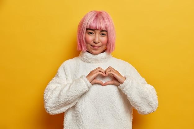 Retrato de mujer hermosa con cabello corto rosa, forma gesto de corazón, expresa amor a alguien, confiesa con simpatía, comparte sentimientos románticos