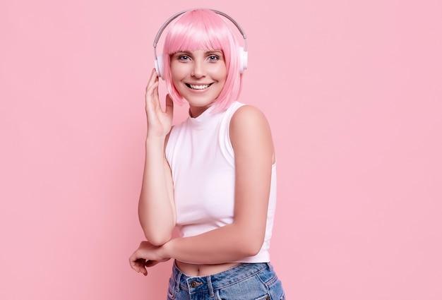 Retrato de mujer hermosa con cabello rosado disfruta de la música en auriculares