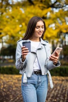 Retrato de mujer hermosa con café leyendo el mensaje en el parque