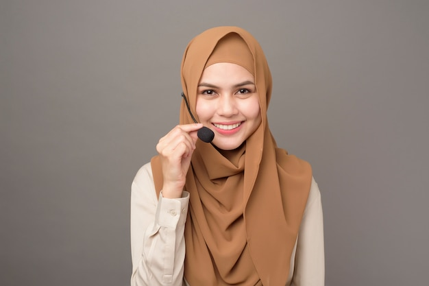 Retrato de mujer hermosa call center con hijab en gris