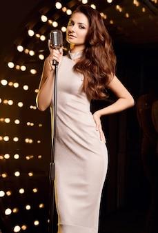 Retrato de mujer hermosa cantante en vestido elegante con micrófono retro en focos de escenario de restaurante.
