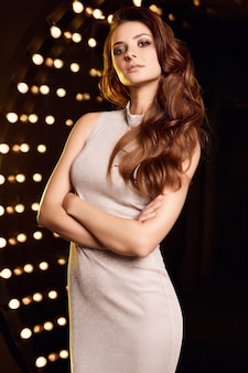 Retrato de mujer hermosa cantante en vestido elegante posando en focos de escenario de restaurante.